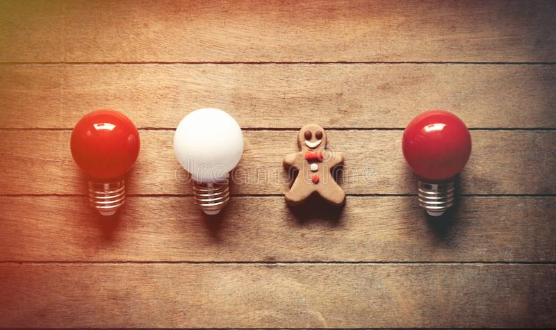 Christmas gingerbread man nad bulbs. On wooden background stock photos