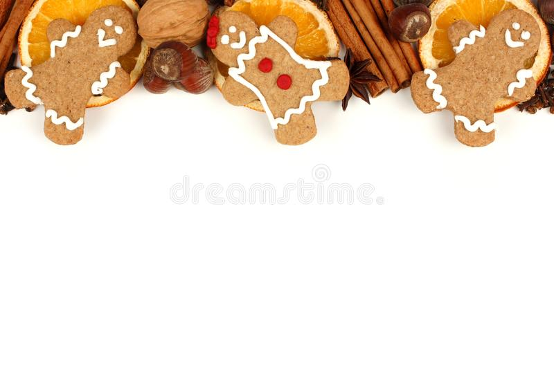 Christmas gingerbread men border with holiday spices over white. Top border of Christmas gingerbread men and holiday spices over a white background stock photo