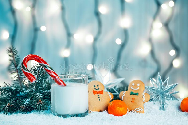 Christmas gingerbread and milk with decorations, snow, christmas tree branches on bokeh blurred lights background royalty free stock photo