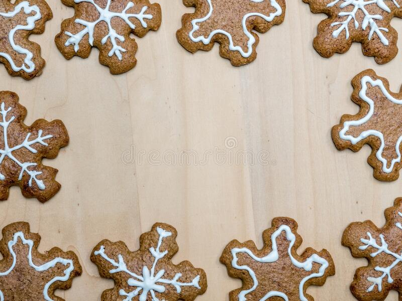 Christmas gingerbread snowflake-shaped cookies. With white icing arranged in frame on wooden rustic board shot from above royalty free stock images