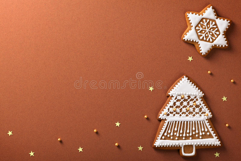 Christmas gingerbreads. Composition with golden stars and balls on brown paper background stock image