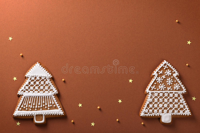 Christmas gingerbreads. Christmas gingerbread trees composition with golden stars and balls on brown paper background royalty free stock images
