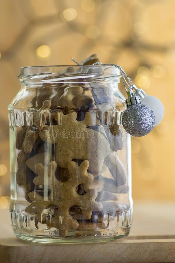 Christmas gingerbreads in glas jar with silver Christmas decorative balls with Christmas lights background royalty free stock photo