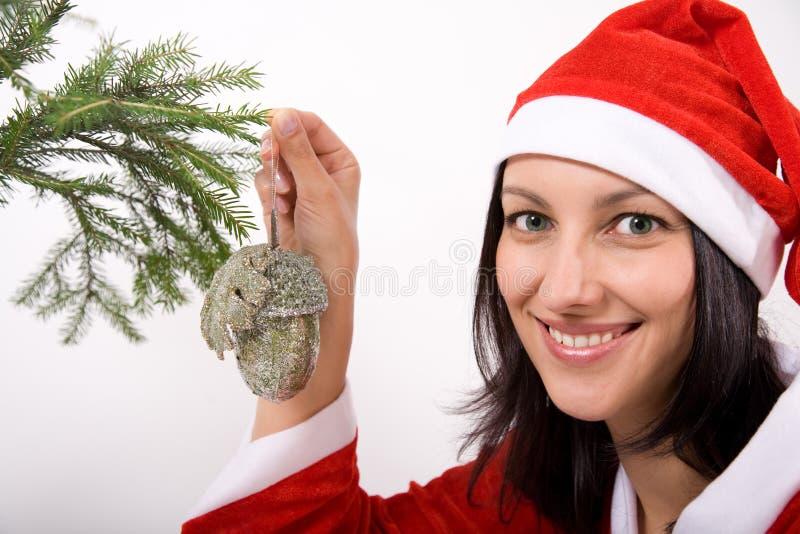 Christmas girl. Santa Claus girl hanging toy on christmas tree stock image