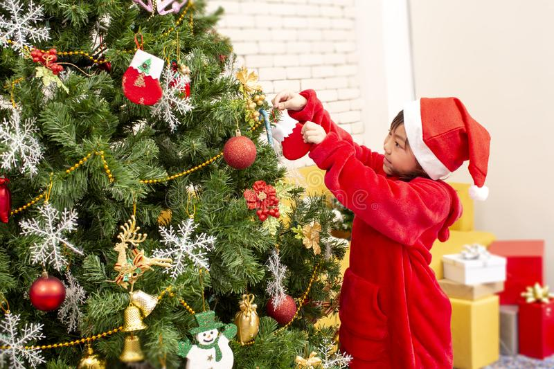 The Christmas girl is decorating the Christmas tree. Kids decorate Xmas tree tree happy children. Happy new year. Children opening. Presents on Xmas eve. Merry royalty free stock images