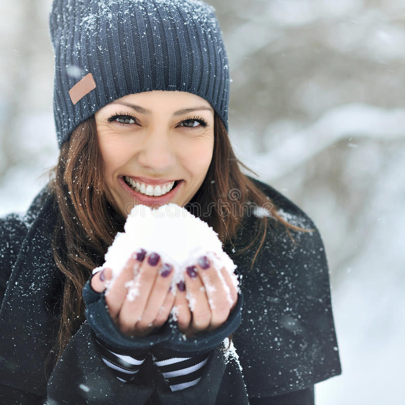 Christmas girl outdoor portrait. Winter woman blowing snow in a stock images