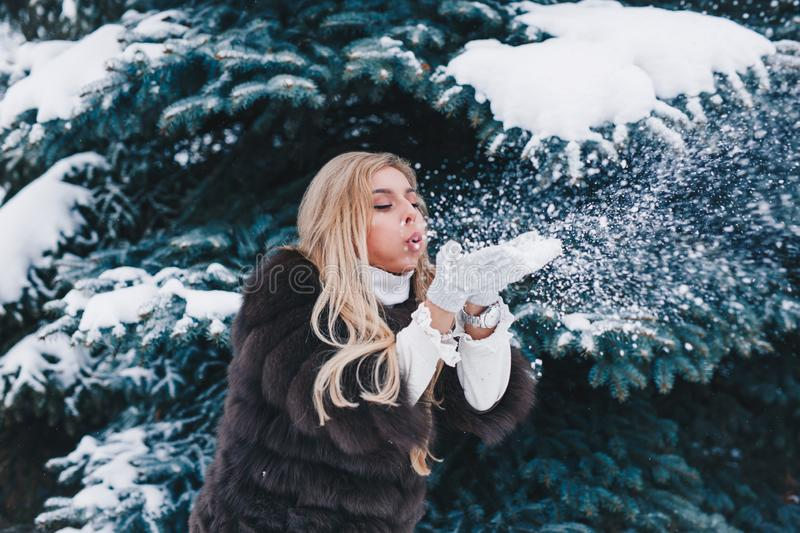 Christmas girl outdoor portrait. Beautiful woman blowing snow in winter forest stock images