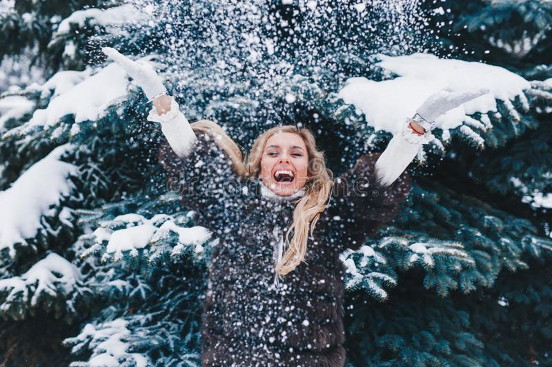Christmas girl outdoor portrait. Beautiful woman blowing snow in winter forest royalty free stock photos