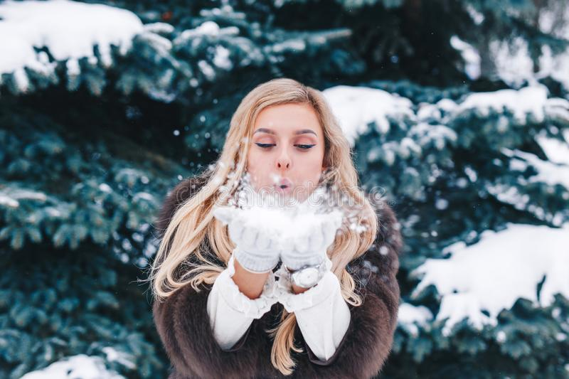 Christmas girl outdoor portrait. Beautiful woman blowing snow in winter forest stock image