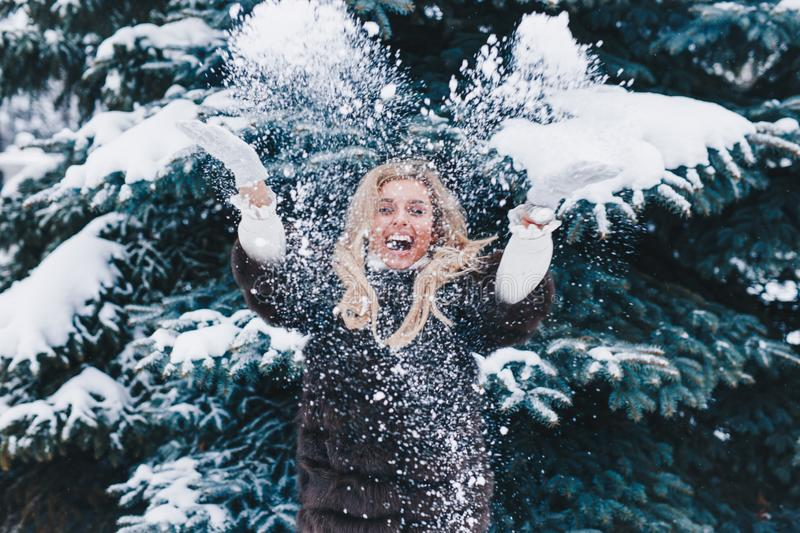 Christmas girl outdoor portrait. Beautiful woman blowing snow in winter forest stock photo