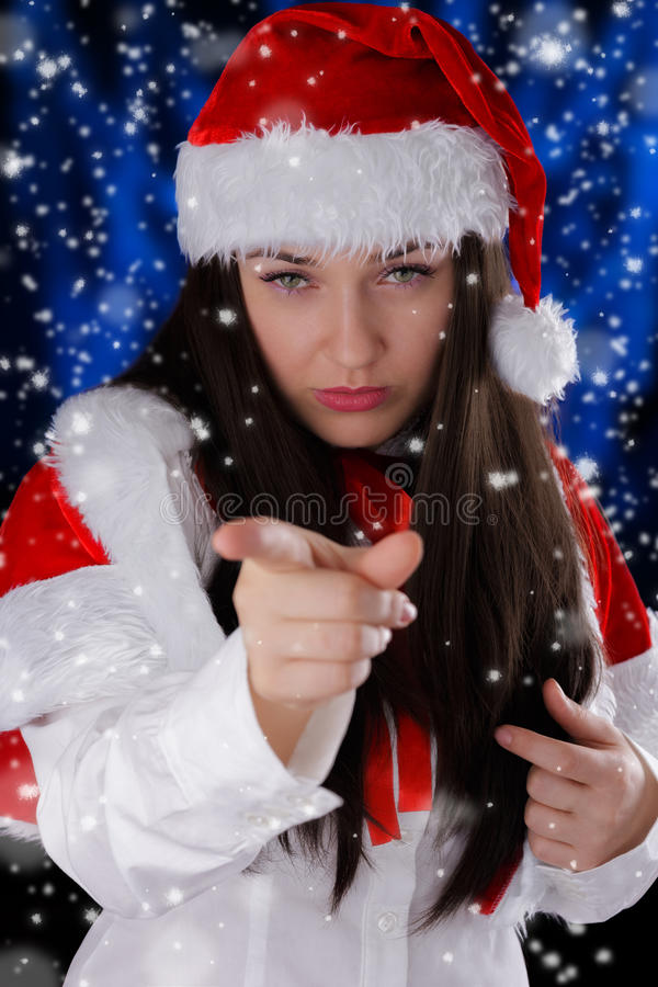 Christmas Girl Pointing. Beautiful girl pointing at the viewer with snow falling around her royalty free stock images