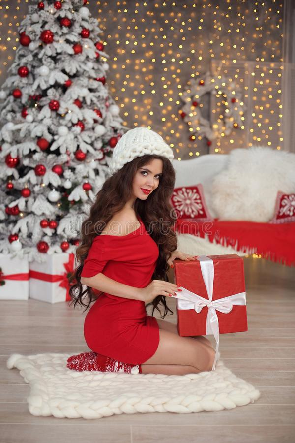 Christmas girl portrait in winter hat. Beautiful santa woman present gift box. Smiling brunette in red with long hair sitting on royalty free stock image
