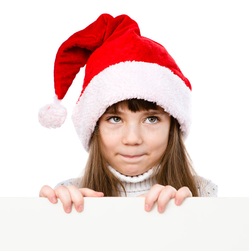 Christmas girl in santa helper hat peeping from behind empty board and looking up. isolated on white background royalty free stock image