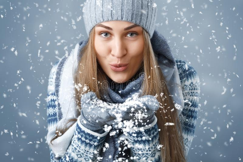 Christmas. A girl in winter clothes blowing on the snow. stock image