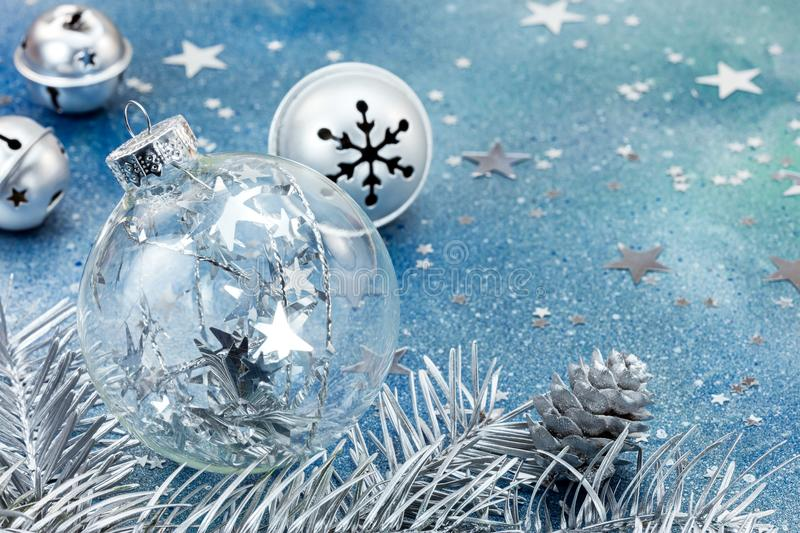 Christmas glass ball and silver jingle bells on blue background stock images