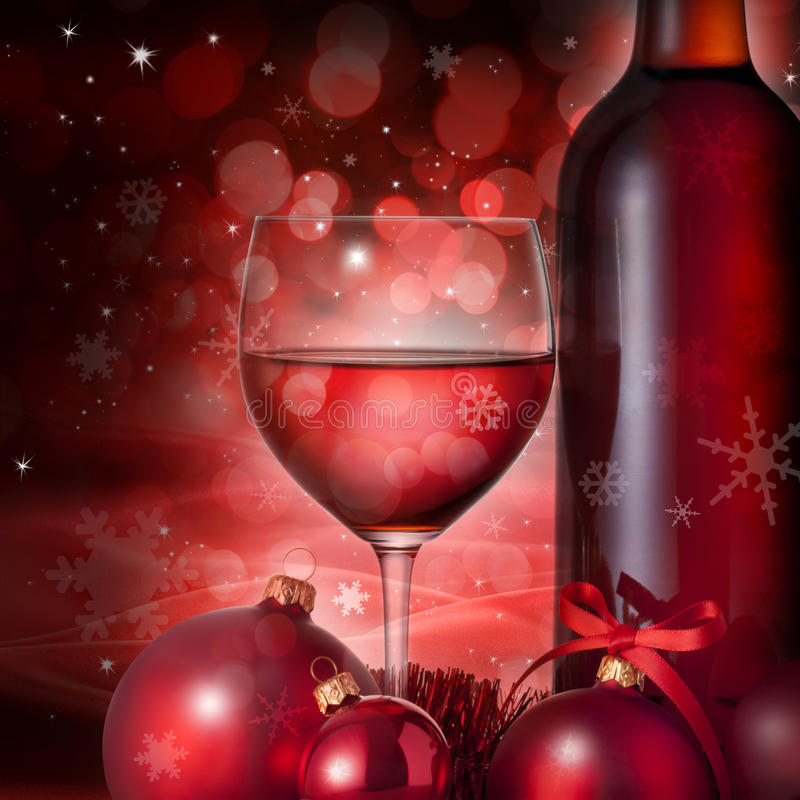 Christmas Glass Red Wine Background. A close up of a bottle and glass of red wine with christmas ornaments, ribbon and tinsel on a red Christmas background. Can