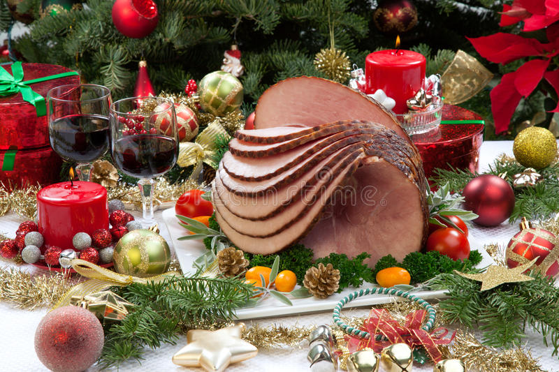 Christmas Glazed Ham. Christmas dinning table with glazed roasted ham with tomatoes, herbs, and kumquats. Surrounded by Christmas ornaments, gifts, candles, and stock image
