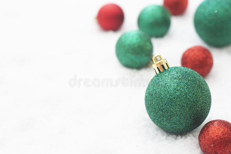 Christmas glitered green and red baubles, balls isolated on snow. Winter greeting card with copy space. For text, background, design, sparkle, glow, bow, shiny stock images