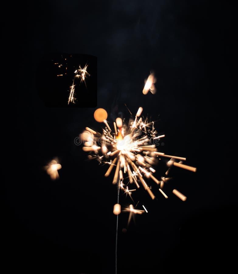 Christmas glittering sparklers over black background. Xmas festive decoration lighting element. Magic golden sparks lights royalty free stock photos