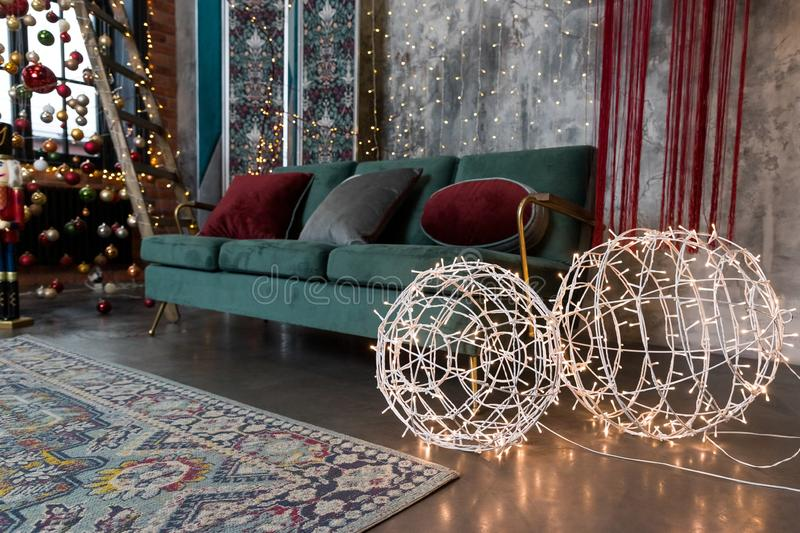 Christmas glowing garland on shape of balls. Beautiful lighting lamps. Colorful lights , green sofa in living room stock photos