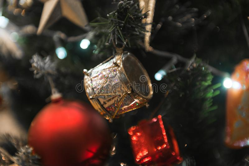 Christmas gold Drum hanging on a beautiful Christmas tree close view and macro. Christmas gold Drum hanging on a beautiful Christmas tree surrounded by stock photos