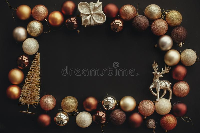 Christmas gold frame of gift box, tree, reindeer and glitter baubles on stylish black background. Christmas flat lay with space f stock photos