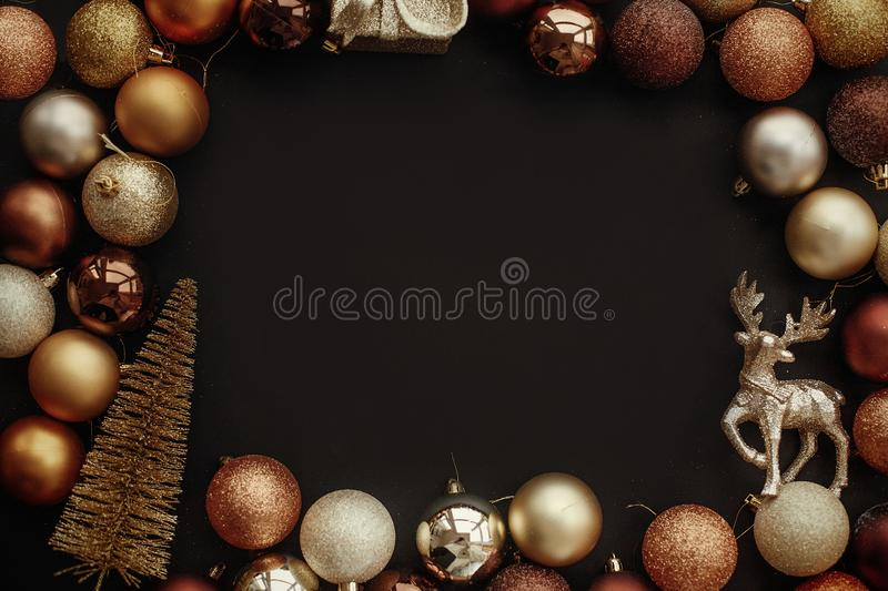 Christmas gold frame of gift box, tree, reindeer and glitter baubles on stylish black background. Christmas flat lay with space f. Or text. Seasons greetings stock image