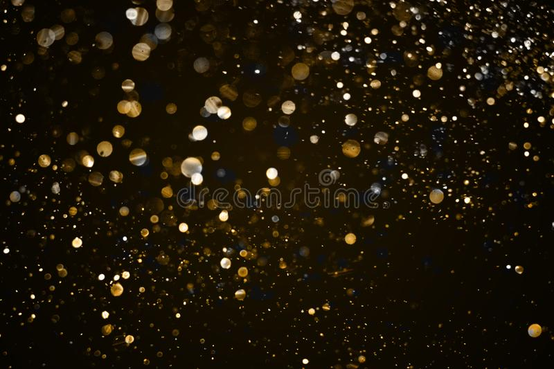 christmas gold sparkle glitter explosion dust particles background with bokeh, gold holiday happy new year and valentine day stock photos