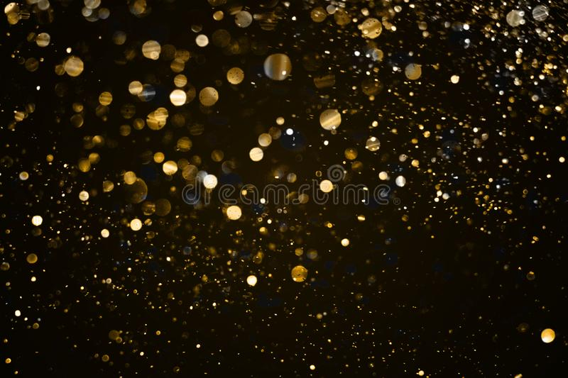 christmas gold sparkle glitter explosion dust particles background with bokeh, gold holiday happy new year and valentine day stock photography