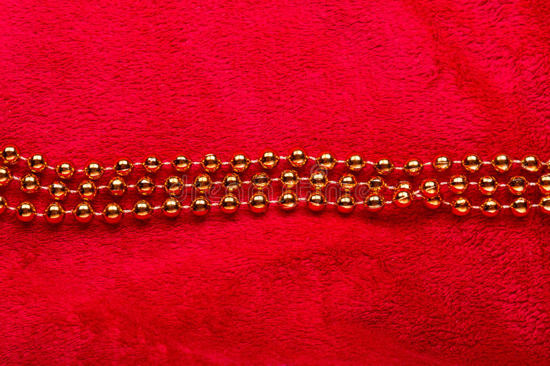 Christmas golden beads on red background royalty free stock photography