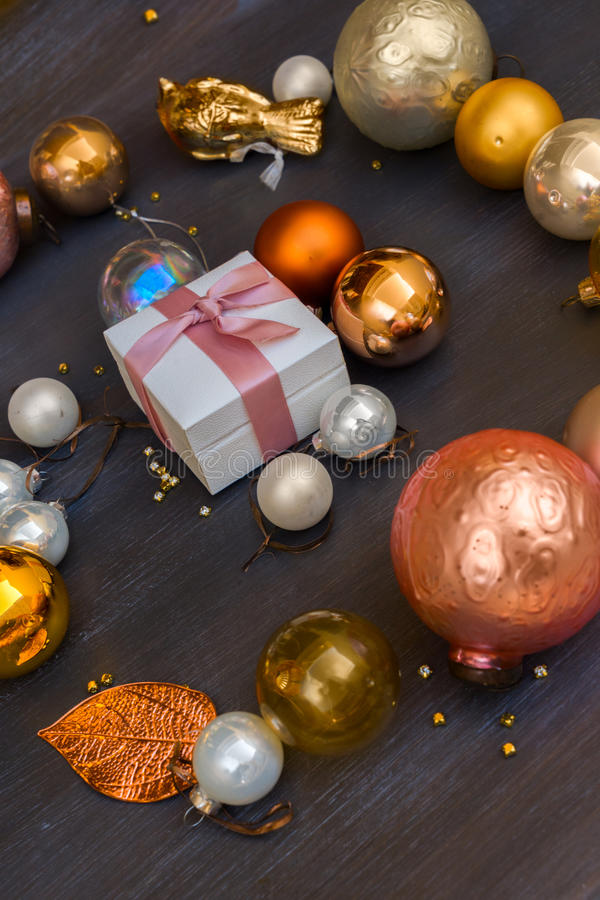 Christmas golden decorations. Christmas golden and silver decorations on dark wooden background with white gift box royalty free stock photo
