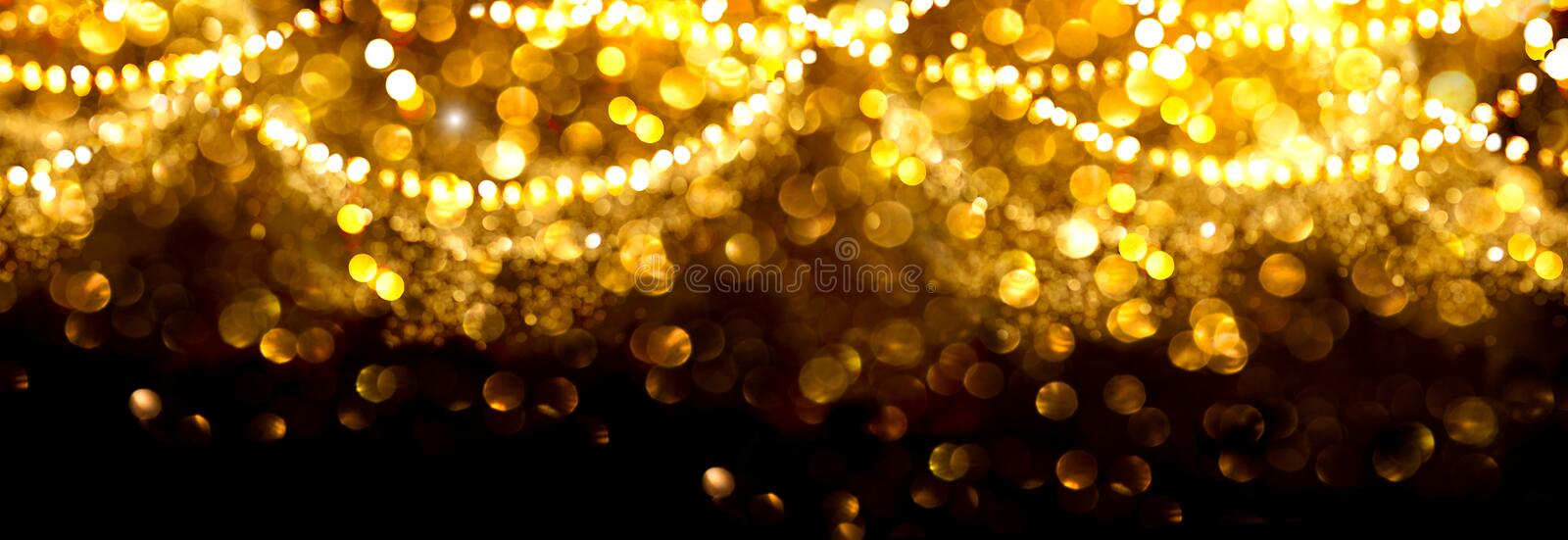 Christmas golden glowing background. Gold holiday abstract glitter defocused backdrop with blinking stars and garlands stock photos