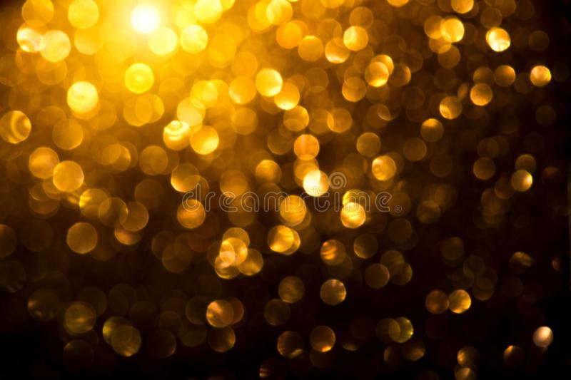 Christmas golden glowing background. Holiday abstract defocused backdrop. Tinsel blurred gold bokeh on black. Background royalty free stock photography