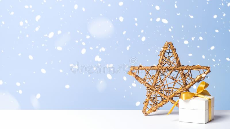 Christmas golden star decoration and Xmas present in snow on blue background with copy space. Christmas, New Year, winter holidays royalty free stock photography