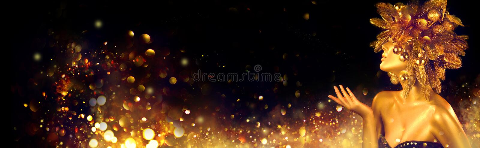 Christmas golden Woman. Winter girl pointing Hand, blowing blinking stars, Beautiful New Year, Christmas Tree Holiday Hairstyle stock photo