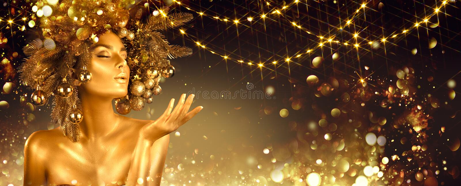 Christmas golden Woman. Winter girl pointing Hand, blowing blinking stars, Beautiful New Year, Christmas Tree Holiday Hairstyle royalty free stock photos
