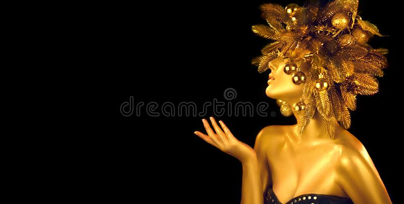 Christmas golden Woman. Winter girl pointing Hand, blowing, holding product Beautiful New Year, Christmas Tree Holiday Hairstyle stock image