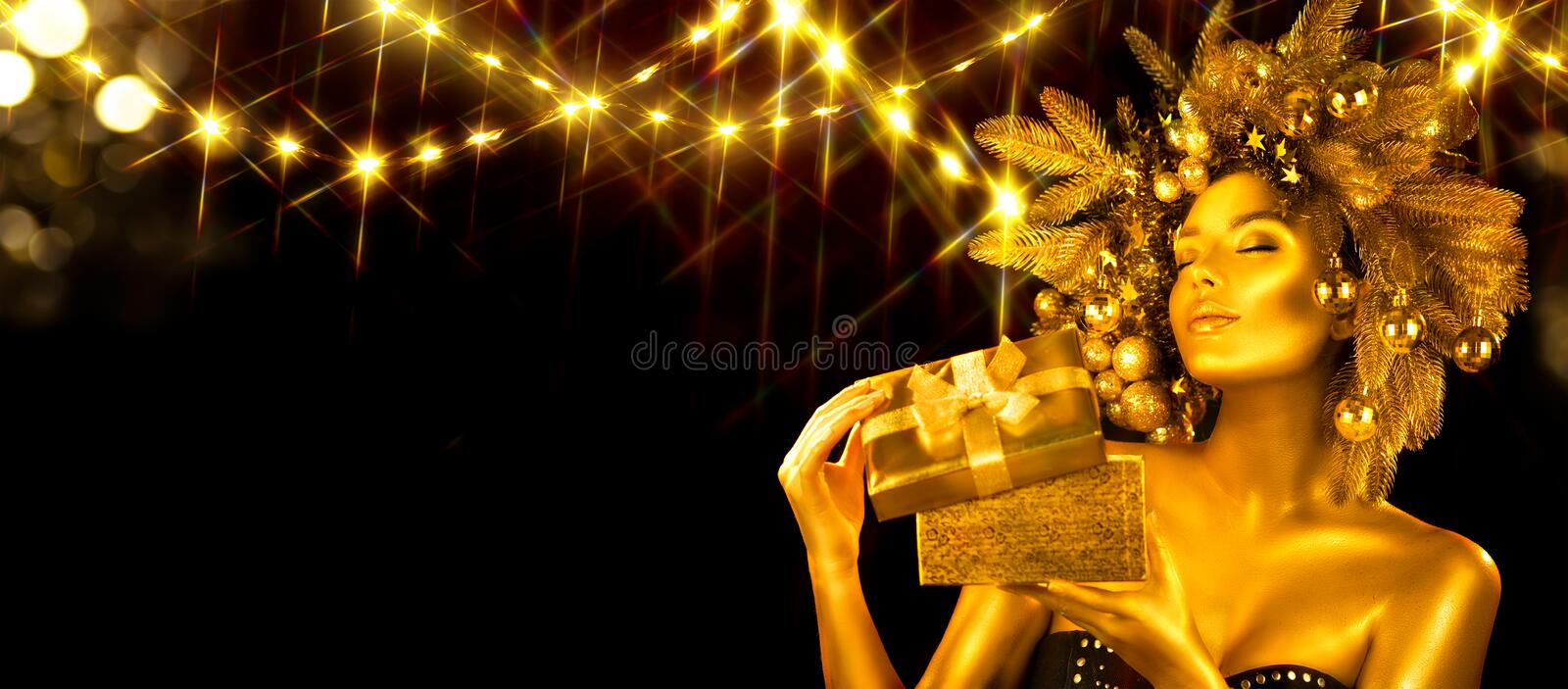 Christmas golden Woman. Winter girl receiving gift, opening magic box, Beautiful New Year, Christmas Tree Holiday Hairstyle stock images