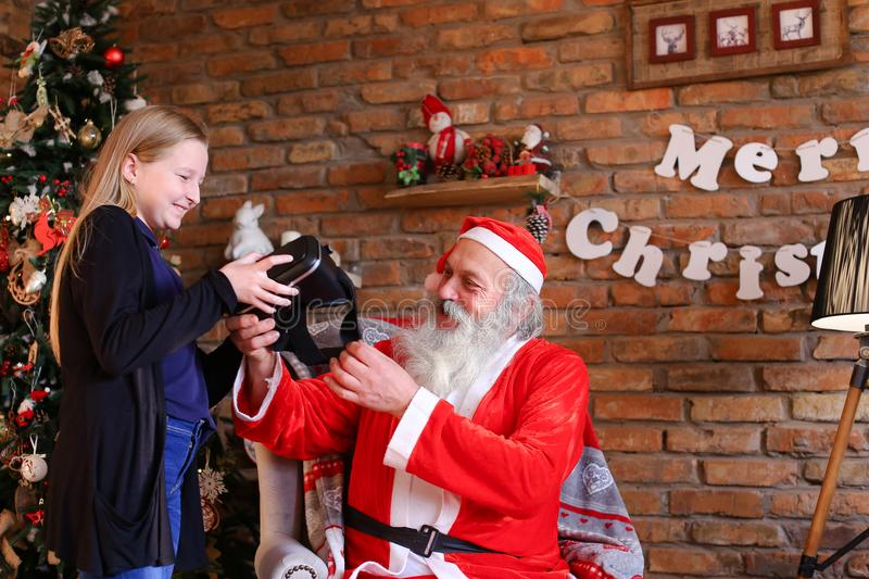 Happy girl happy to receive from Santa Claus Christmas gift in f. Christmas grandfather with great pleasure gives long-awaited surprise to cheerful female child royalty free stock photography