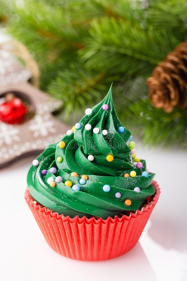 Christmas green cupcake in red cup. Christmas green cupcake with colorful sprinkles in red cup on white background with decorations stock images