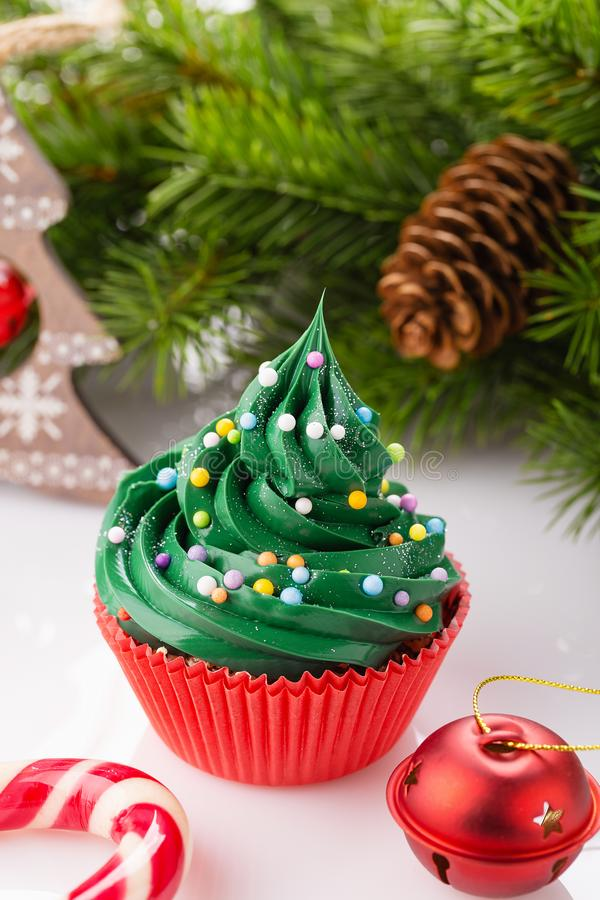 Christmas green cupcake in red cup. Christmas green cupcake with colorful sprinkles in red cup on white background with decorations royalty free stock photography