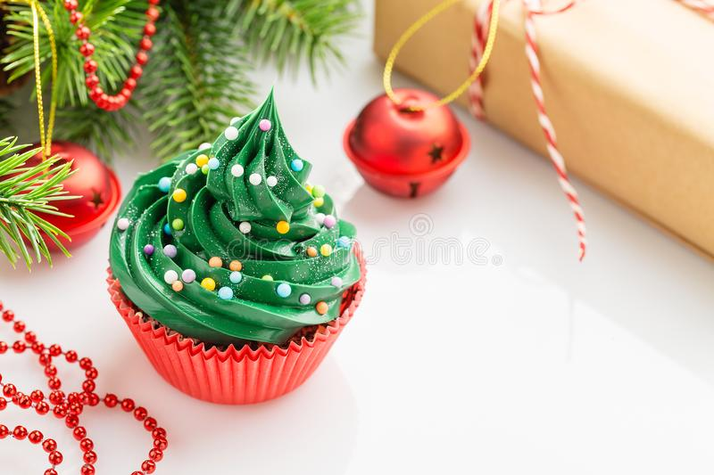 Christmas green cupcake in red cup with decorations. Christmas green cupcake with colorful sprinkles in red cup on white background with decorations. Copy space stock photos