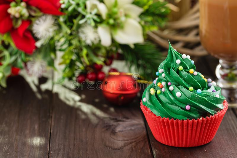 Green christmas cupcake in red cup with decorations. Christmas green cupcake with colorful sprinkles in red cup on wooden background with festive decorations stock image