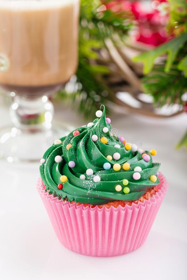 Christmas green cupcake in pink cup. Green christmas cupcake with colorful sprinkles in pink cup on white background with festive decorations and glass of coffee royalty free stock images