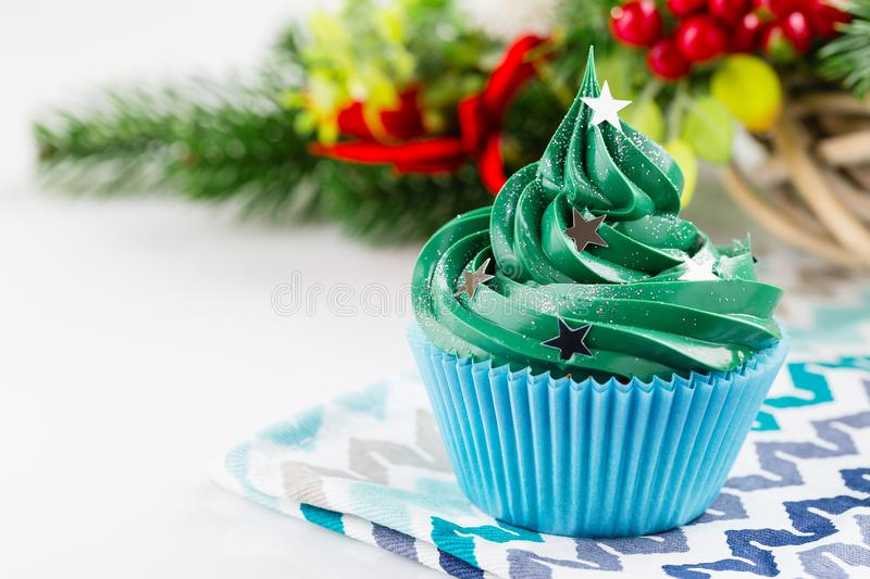 Green christmas cupcake with festive decorations. Christmas green cupcake with star sprinkles in blue cup on white background with festive decorations royalty free stock image