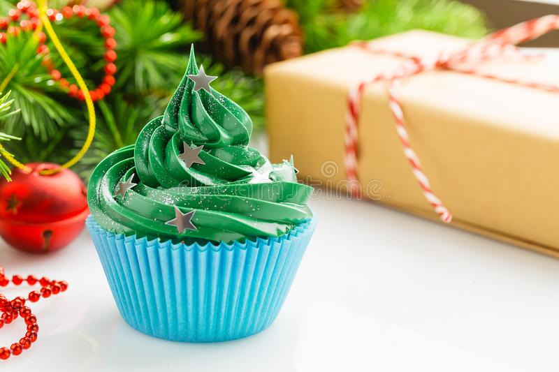 Green christmas cupcake with festive decorations. Christmas green cupcake with star sprinkles in blue cup on white background with festive decorations royalty free stock photography