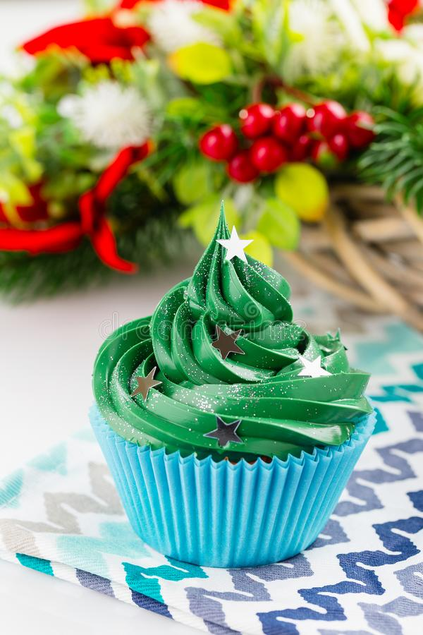 Green christmas cupcake with festive decorations. Christmas green cupcake with star sprinkles in blue cup on white background with festive decorations royalty free stock photo