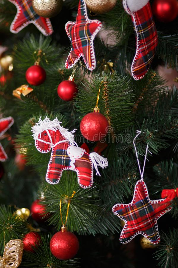 Christmas green pine tree decorated with red colourful toys stars balls sox and horse in studio shoot scene of new year holiday de. Corations royalty free stock image
