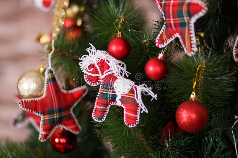 Christmas green pine tree decorated with red colourful toys stars balls sox and horse in studio shoot scene of new year holiday de. Corations stock photography