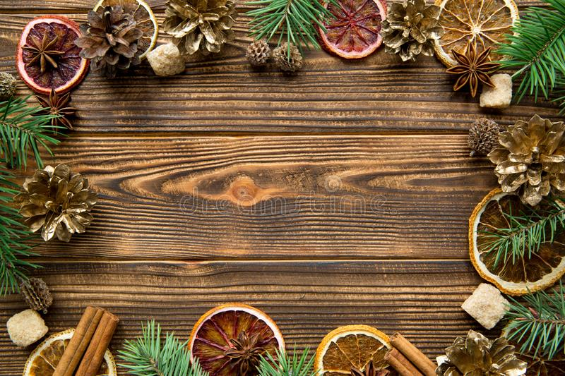 Christmas greeting card backgroun. Dried oranges, spice, fir tree branches frame on wooden brown table background. Copy-space. Christmas greeting card backgroun stock photos